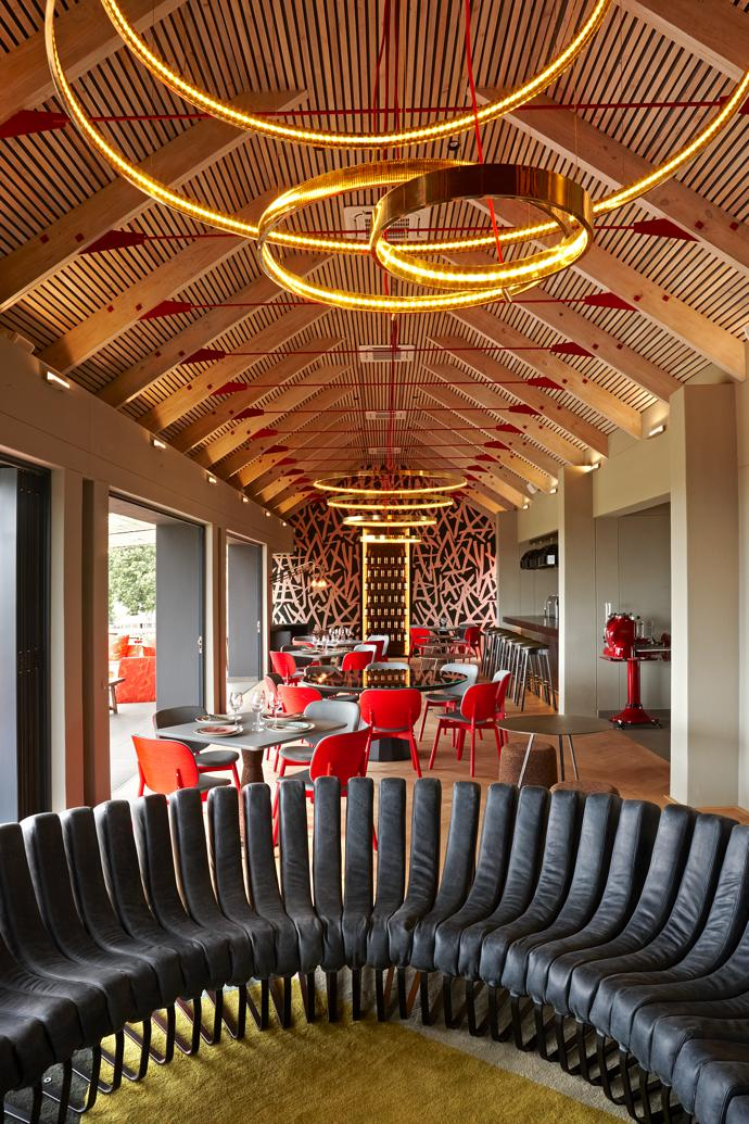 Brass halo lights lead the eye to the Sarah Ord Crayolla wallpaper, its bold brushstroke pattern echoing the Kunjani! Wines logo. Haldane Martin Sim-ply chairs add pops of accent red.