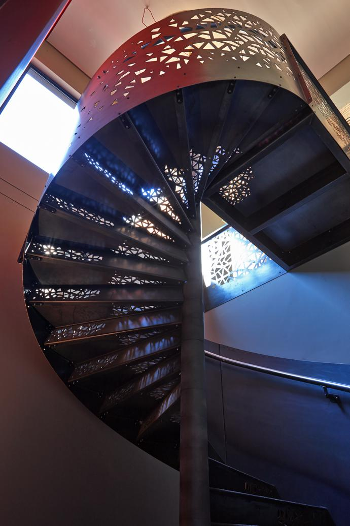The spiral staircase leading down to the cellar has Voronoi pattern cutouts to evoke a descent into the Earth.