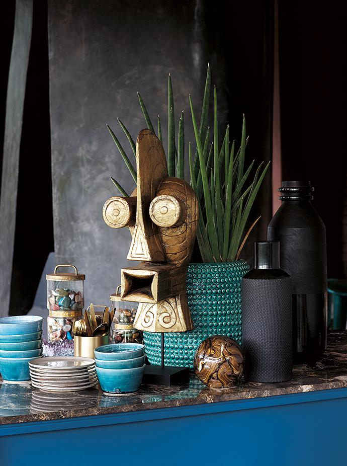 A striking gold mask by Out of this World stands on the bar with a planter and paper-weight by Cécile & Boyd.