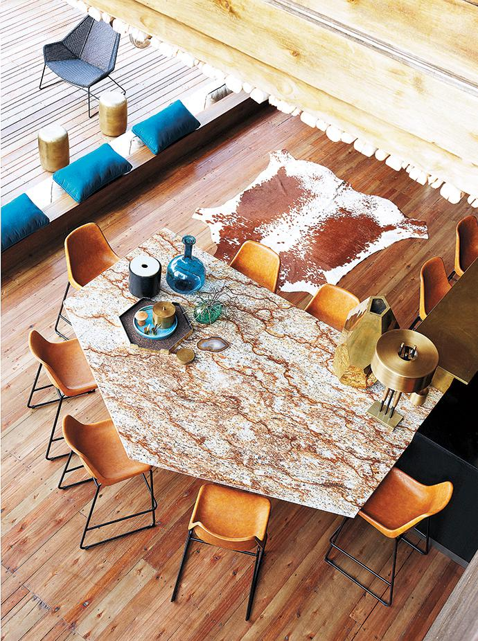 On the central terrace, wood and tan leather are accented with touches of gold. The geometric tabletop is made of a Verniz Tropical granite slab. The chairs are from Chair Crazy.