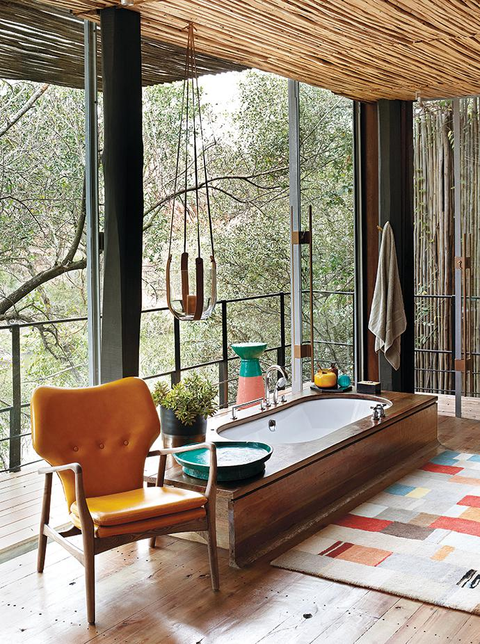 A bath with a view is evidence of the attempt to blur building boundaries and extend the property as far as possible into the wilderness. The statement walnut timber chair is by Cécile & Boyd and the leather plant hanger is by Julia Stadler.
