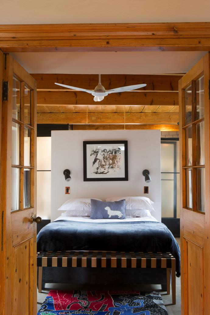 Of the four bedrooms, the two original ones are laid out in a similar symmetrical arrangement, with the bed against a screen wall, beyond which lies the bathroom. The artwork is a Diane Victor charcoal and the rug is a Norman Catherine design.