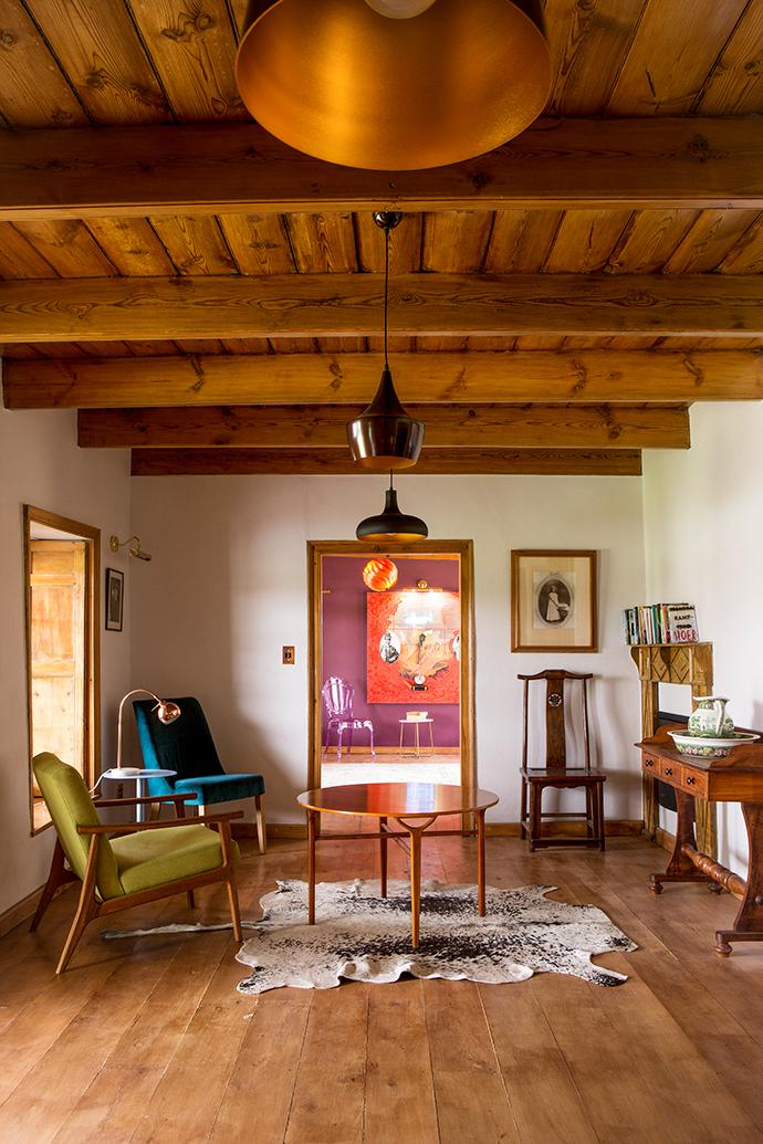 In the original living room, the restored yellowwood floor and ceiling frame an eclectic mix of Scandi, antique and family furniture. The round Ax table is a 1950 Danish piece by Peter Hvidt and Orla Molgaard-Nielsen for Fritz Hansen, from Jeremy Stephens Antiques in Parktown. In the room beyond, a Wayne Barker painting hangs against a lilac-mauve wall. The orange pendant light is a 1967 Turbo by Louis Weisdorf, sourced by Jeremy Stephens Antiques.