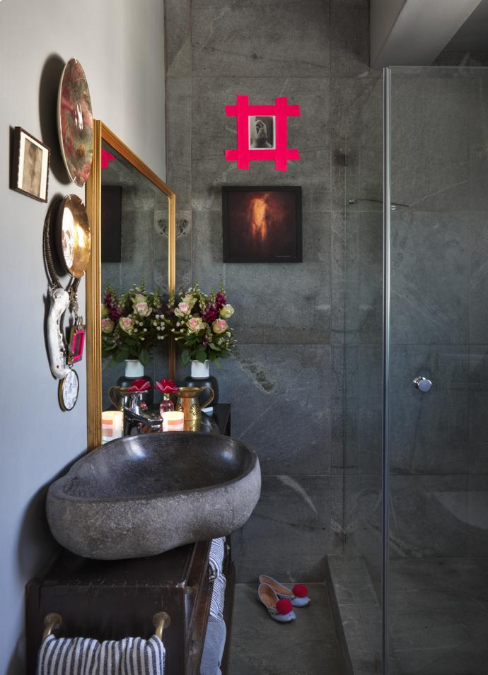 The bathroom features a pebble basin made of granite. The photograph of a hand framed in pink tape is by artist Sanell Aggenbach; the nude is by Pieter Vermaak; the plates are by Theo Kleynhans; and the neckpiece is one of Karien's own designs.
