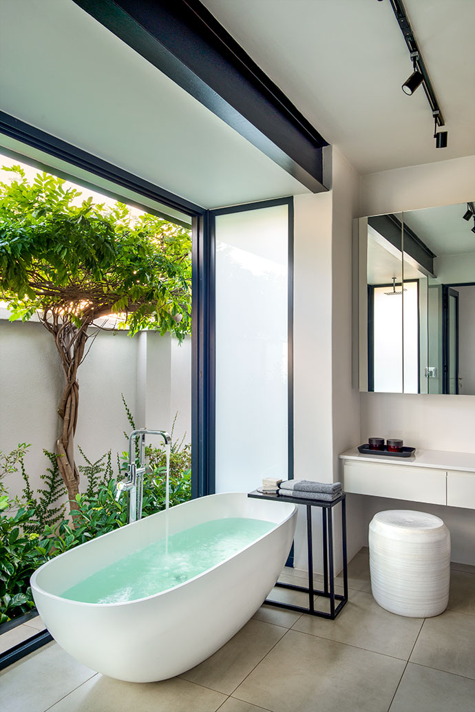 The new main bathroom is a locus of calm, with doors that fold away to reveal a secluded garden. The freestanding bath is from Dado Baths, and it's matched with an old side table of Hendrien's and a white ceramic stool by Anthony Shapiro.