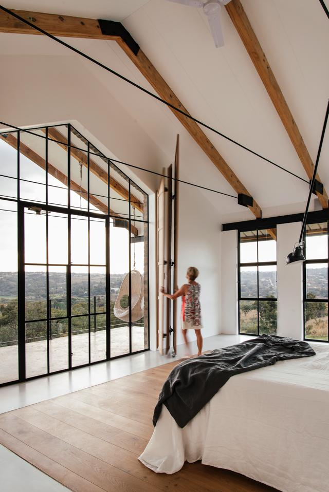The main bedroom affords a magnificent view down the escarpment. The wall-mounted bedside lamp is the Model 265 by designer Paolo Rizzatto for Flos.