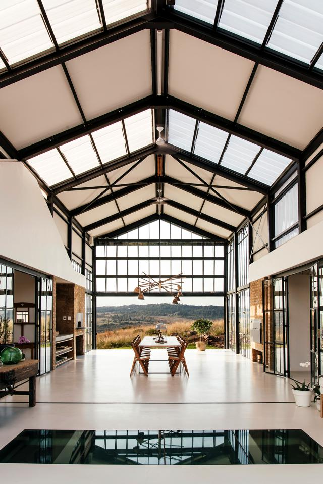 The conservatory with the mechanised glass door open, looking north across the Highveld landscape. Flanking the white oak table are antique school-room chairs. The antique workman's table on the left was found in the old farmhouse on the property.
