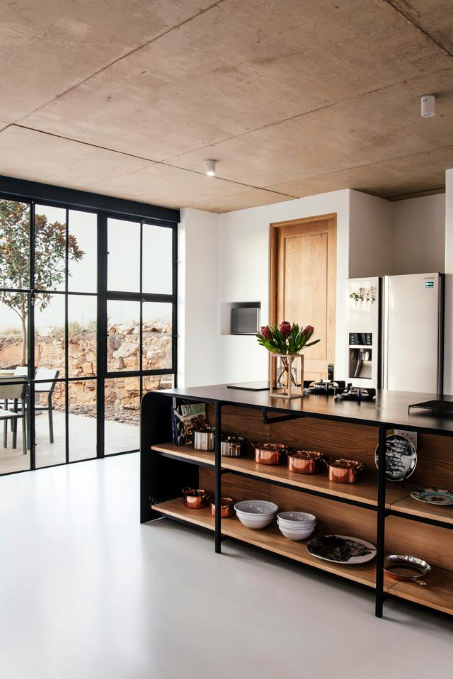 Architect Nadine Engelbrecht designed the kitchen counter and Tsipe Engineering made it. She also designed the timber door, and it was made by Bron Joineries. The cabinet is from Weylandts. Next to the kitchen area is a small coffee lounge with a coffee table and chair from Weylandts.