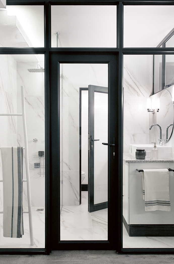 The monochrome wet room visually extends the space.