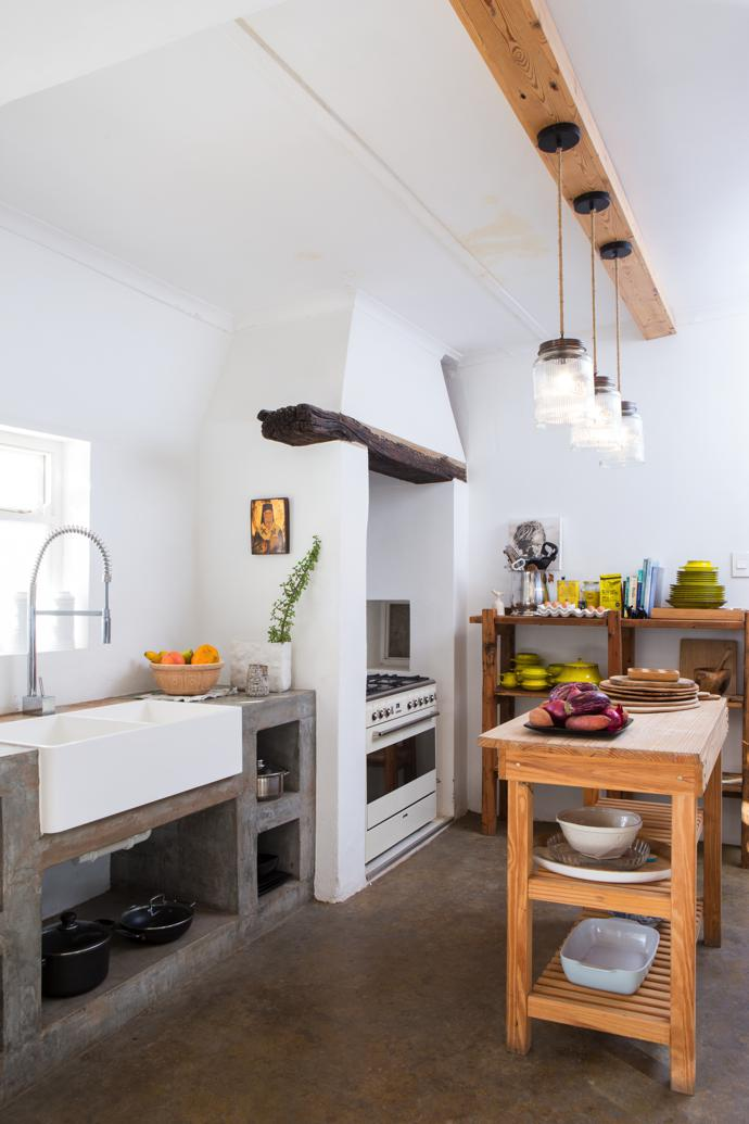 A trio of glass retro cookie jars recycled into pendant lights create a whimsical focal point in the functional farm-style kitchen. A SMEG vintage cream gas oven and hob is installed in the alcove where a wood-burning stove would have stood in Victorian times.