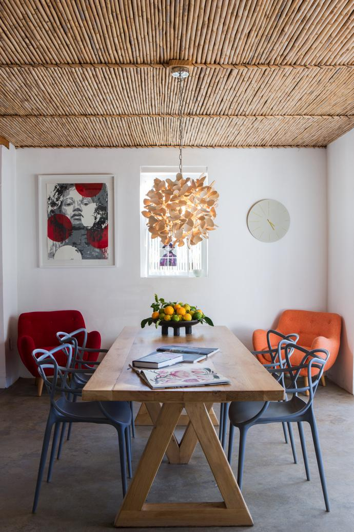 An artwork by Lionel Smit watches over the cranberry and tangerine Anne armchairs from sofacompany.com. An artisan-crafted table, clock from Habitat and organic coconut-shell chandelier complete the picture.