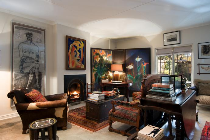 A fireplace is essential in Karoo winters, and the spacious bedsitting room of the cottage also has a large window to admit the winter sun. Come summer, the blinds are lowered and the room is kept in cool darkness. A painting by Michele Redelinghuys hangs above the fireplace and the corner screen is an assembly of works by Leon Vermeulen. Their glowing colours are reflected in the furnishings.