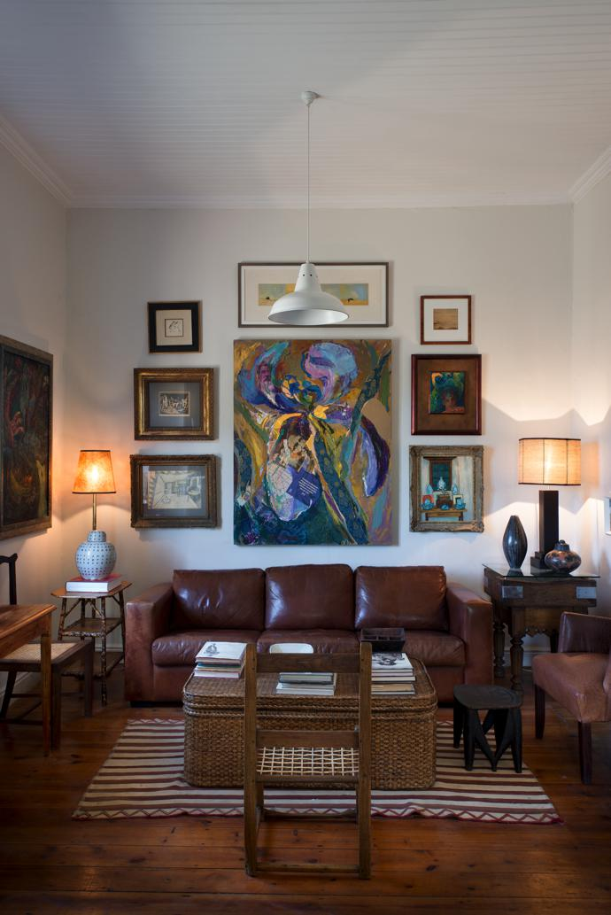 Face to face in the living room of the main house: a leather sofa from Klooftique and a lemoenhout riempie chair. The large painting above the sofa is by Marion Geiger.