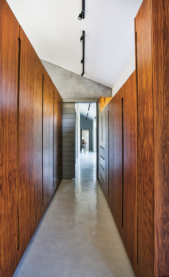 Sleek wooden cupboards in the master bedroom form a warm contrast to the off-shutter concrete walls and screed floors.