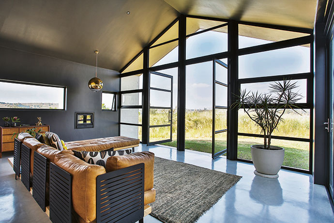 The walls of the main living room are painted dark to form a contrast with the adjoining rooms. The vistas from here are the most spectacular; windows to the west afford framed views of the valley and the Magaliesberg in the distance. The sofa is by GOET Furniture and Design.