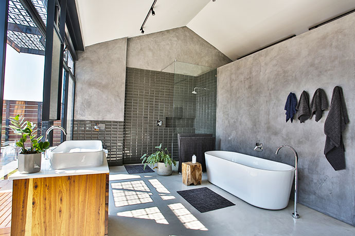 The spacious master bathroom also has large windows, which look out on an enclosed courtyard. The basin is cleverly placed in a freestanding unit right in front of the window to foster the indoor outdoor connection.