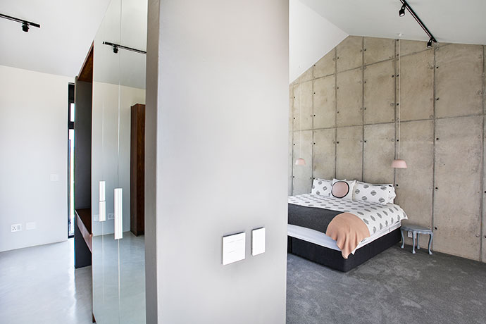The master bedroom features a large off-shutter concrete wall.