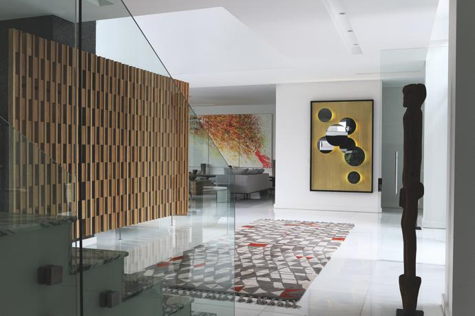 The brass clad Solar Mirror in the entrance, which also features a Bongo Tribal statue and custom Berber rug, was designed by OKHA Director Adam Court who also designed the screen.