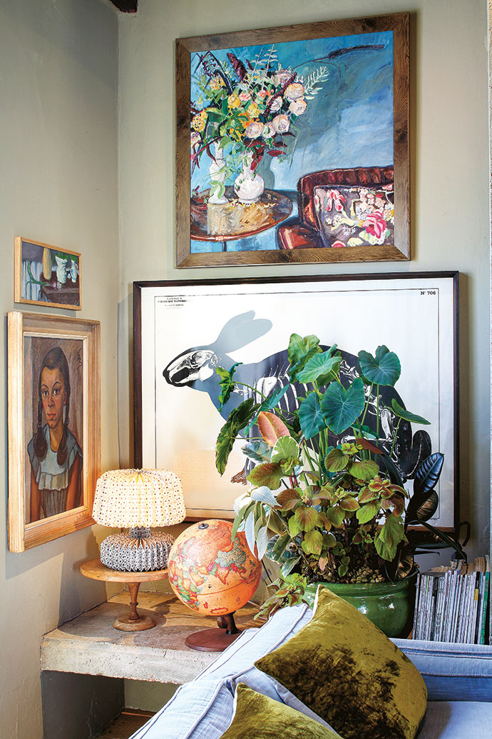 Art and precious objects in the house tell stories of the homeowners' travels and interests. A sketch of a rabbit skeleton from Deyrolle, a famous Paris institution in the field of taxidermy and natural sciences; above it a painting by Dané Erwee; a Japanese origami lamp; a vintage globe; and a lush pot plant create an intriguing vignette. | Various flea-market treasures, books and plants are displayed on a locally made steel shelving unit.