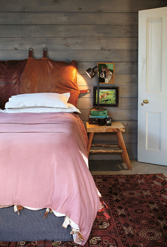 Benoît's love for the boxer dog breed is evident in the main bedroom, where a cracked wall was clad with wooden panelling. The leather bag headboard was custom-made.