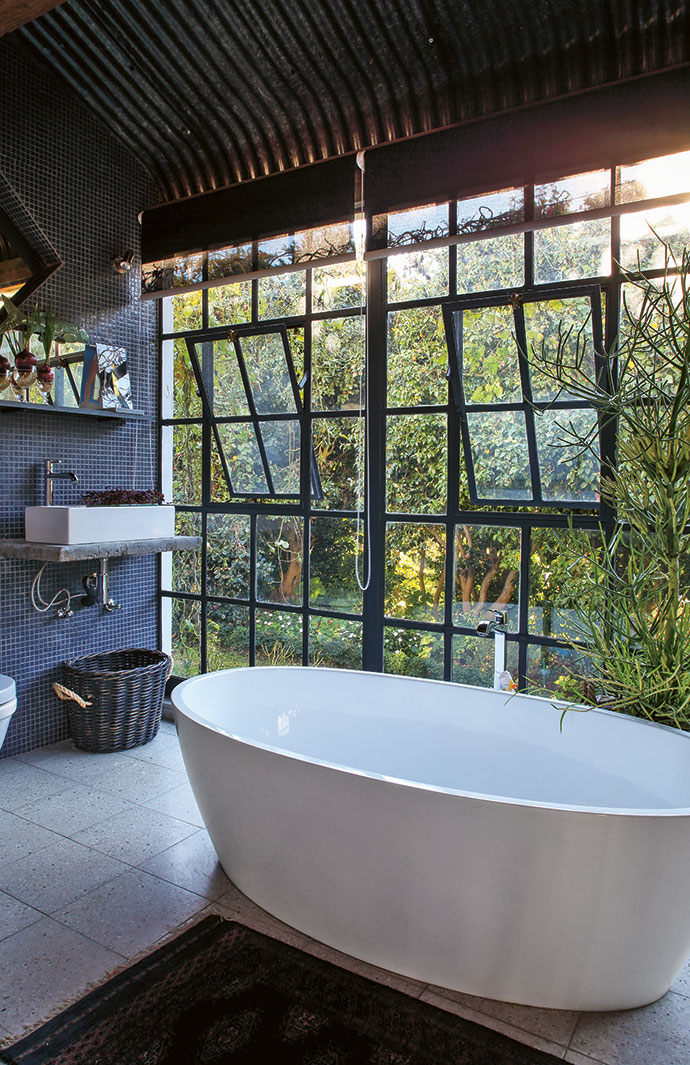 The main bathroom on the former covered stoep still has the original moulded corrugated iron roof, exposed on the inside. New school windows make for an idyllic view of the garden from the bath, especially at night.