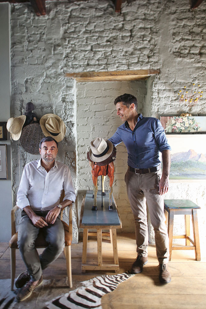 Homeowners Louis Orlianges and Benoît Thomas in front of the original back door. The painted clay bricks were exposed during the renovation process.
