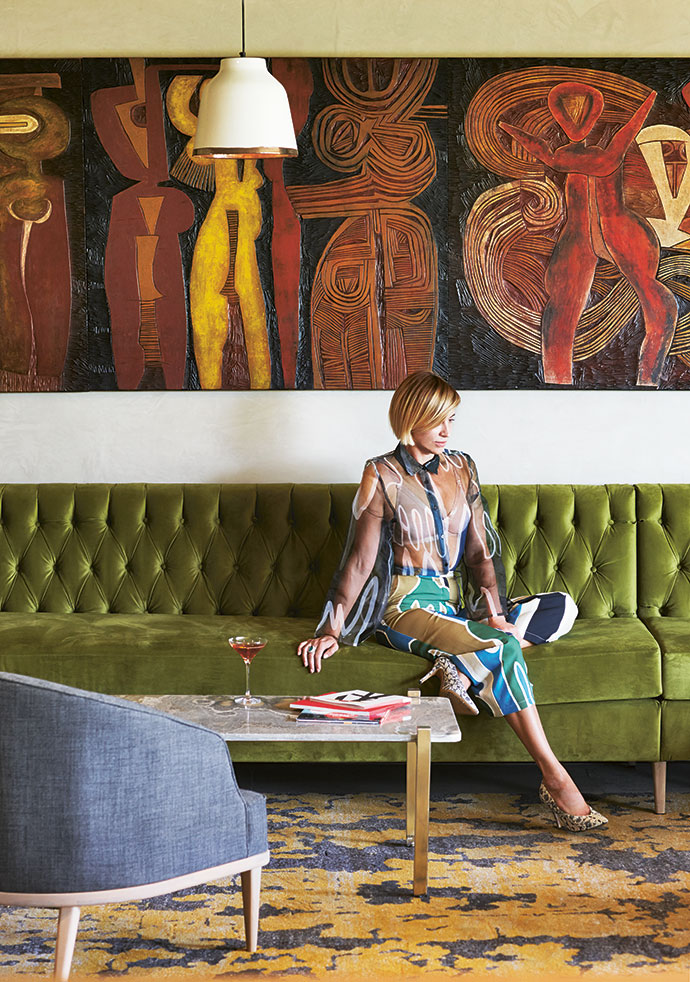 The Progression by Cecil Skotnes is a series of 11 carved, incised and painted wooden panels that he created in 1971. The panels adorn the walls of the Skotnes Bar. Natalie is wearing an outfit by local fashion designer Rich Mnisi.