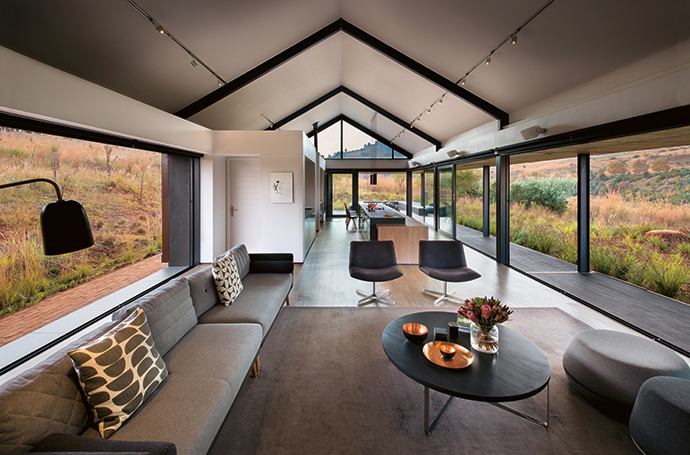 Views feature on three sides of the spare barn structure. The living-room furniture includes a sofa from Sofacompany, a coffee table by Mezzanine and occasional chairs from Weylandts.