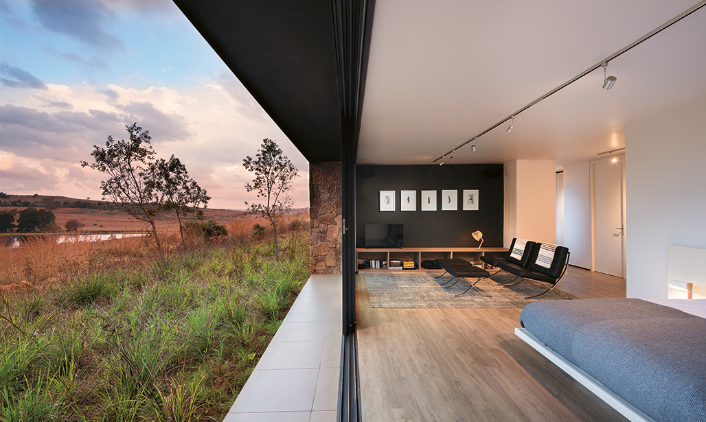 Set back into the slope and with green roofs, the bedrooms have an intimate connection with the landscape. The Barcelona chairs and footstools are from Chair Crazy and the wood-look vinyl floor is from mFLOR. FEATURE