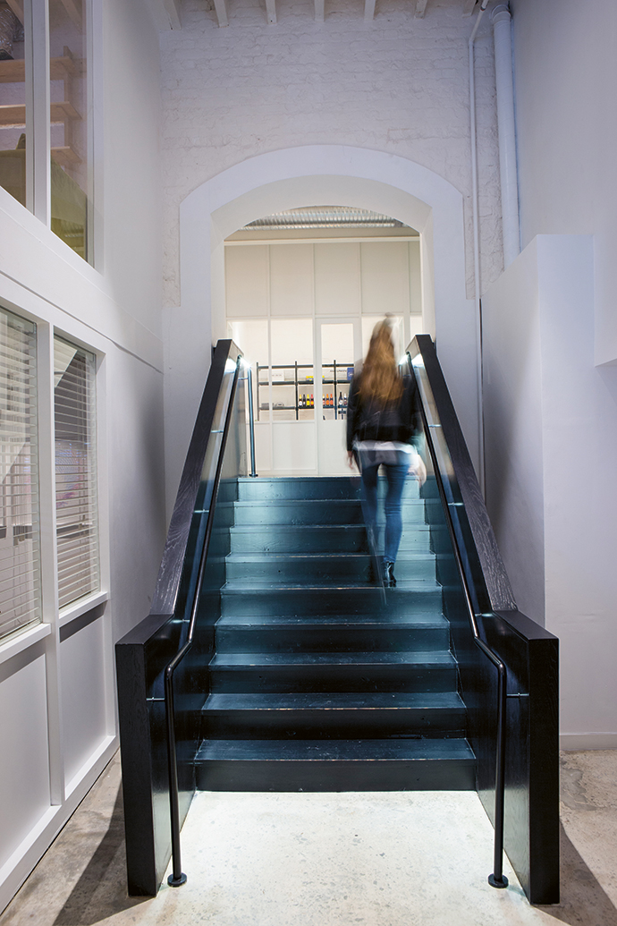 The contrasting black staircase leads from the lobby and boardrooms on the ground floor to the work lounge and suites on the mezzanine level.