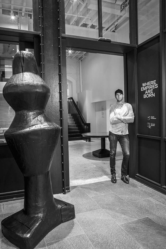 Justin is standing next to a sculpture by Cameron Platter.