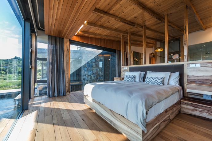 The bedrooms were planned so the bed affords the best possible view of the landscape, with all the other elements located behind it. Furniture such as the bed and the flooring were made using indigenous hardwood timber from forests earmarked for clearing.