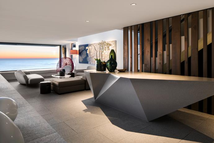 The bar and bar lounge is suspended over the pool and incorporates the Curator couch by OKHA, Dragnet lounge chair by Kenneth Cobonpue and artwork by Martie Kossatz.