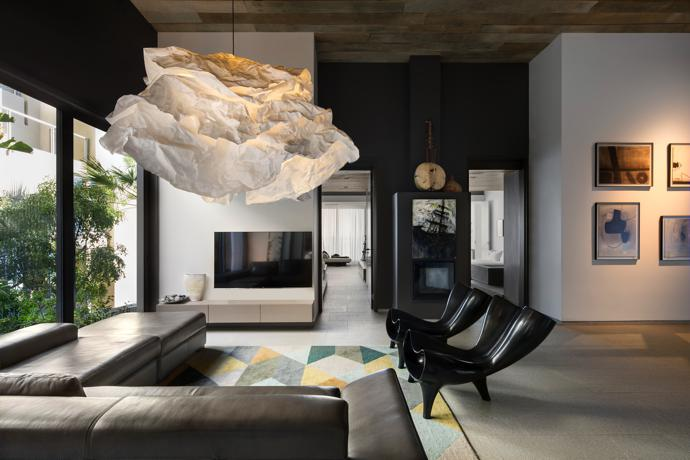 In the pyjama lounge there are two Orgone chairs by Marc Newson that sit below the Cloud Lamp by Margie Teeuwen. A collection of artwork by Charles Gassner hang on the wall.