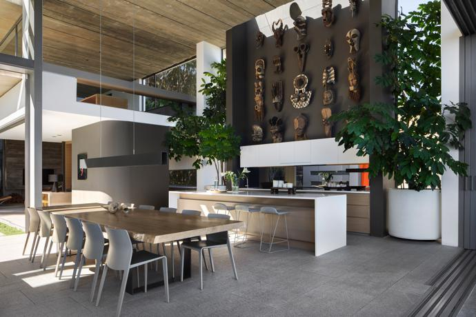 On the living level the front of house integrates the kitchen and dining room areas. The French oak dining table is by Pierre Cronje and Etch Bar stools are by OKHA. The mask wall features a collection of Central and West African masks.