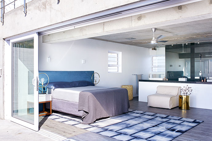 """Splashes of blue, like the leather headboard, and accents in gold and yellow add interest in the bedroom. """"We used lots of natural textures so the house doesn't feel too cold and clinical,"""" says Jaco."""