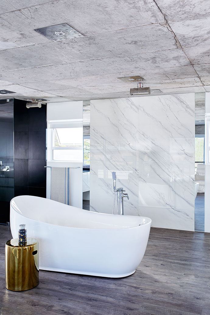 In the master suite, smooth surfaces such as a large marble slab are contrasted with wooden flooring for some warmth.