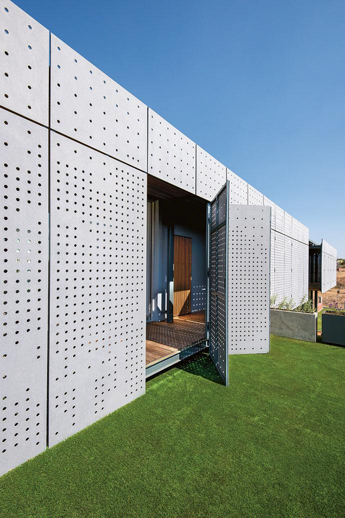 The upstairs balconies lead to roof gardens with artificial grass and planters, adding another dimension to the complex indoor-outdoor relationship.