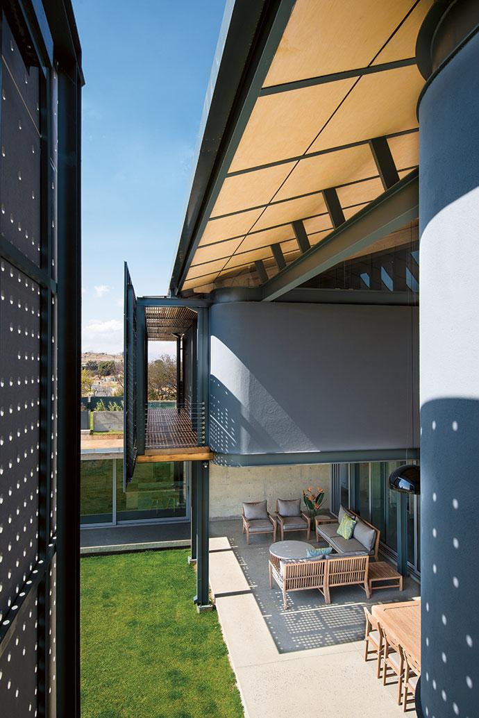 """The bedrooms are housed in two """"boxes"""" suspended above the living areas, giving the house a dramatic street presence."""