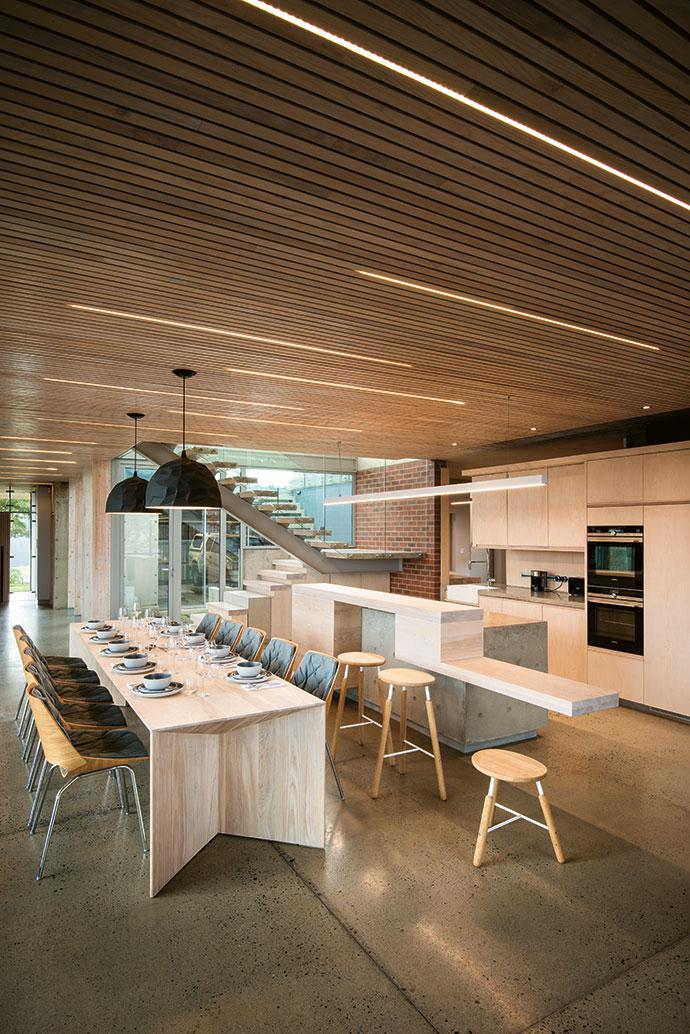 Central to the open-plan living area is the kitchen and dining area. The long dining table is a bespoke design by architect André Eksteen, inspired by folded paper.
