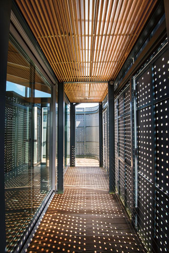 Light filters through the fibre-cement screens drawn across the balconies.