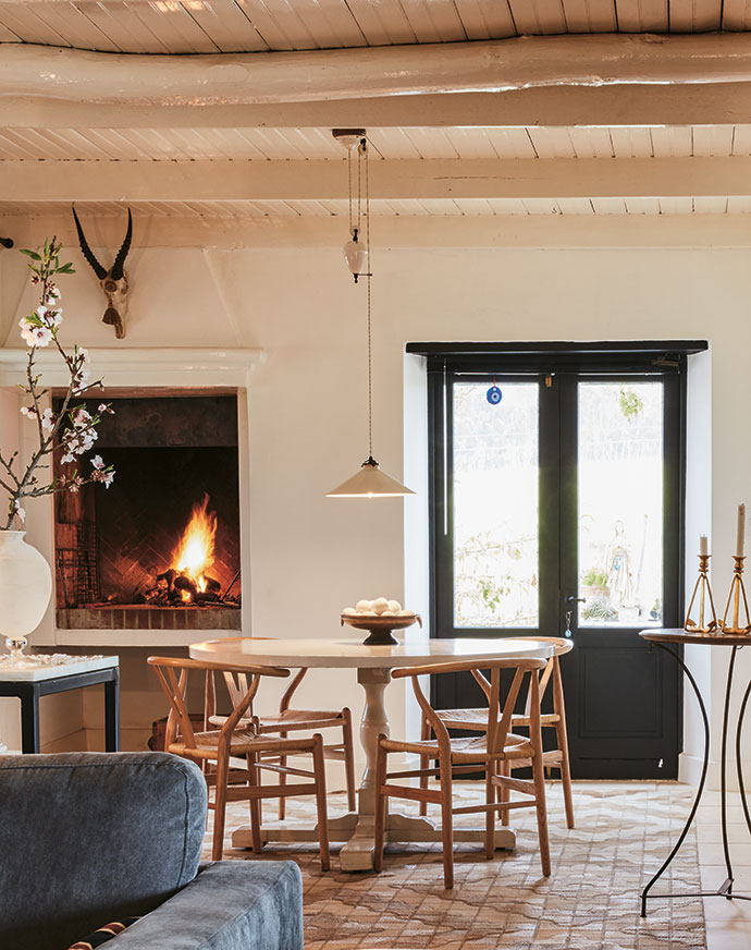 The fireplace used to be a hearth with a small round oven, and the French doors open onto a little stoep that was once a reservoir into which rainwater ran from the roof. The rug is by Johno du Plessis. On the table is a bowl of eggs from the gaggle of about 200 geese on the farm.