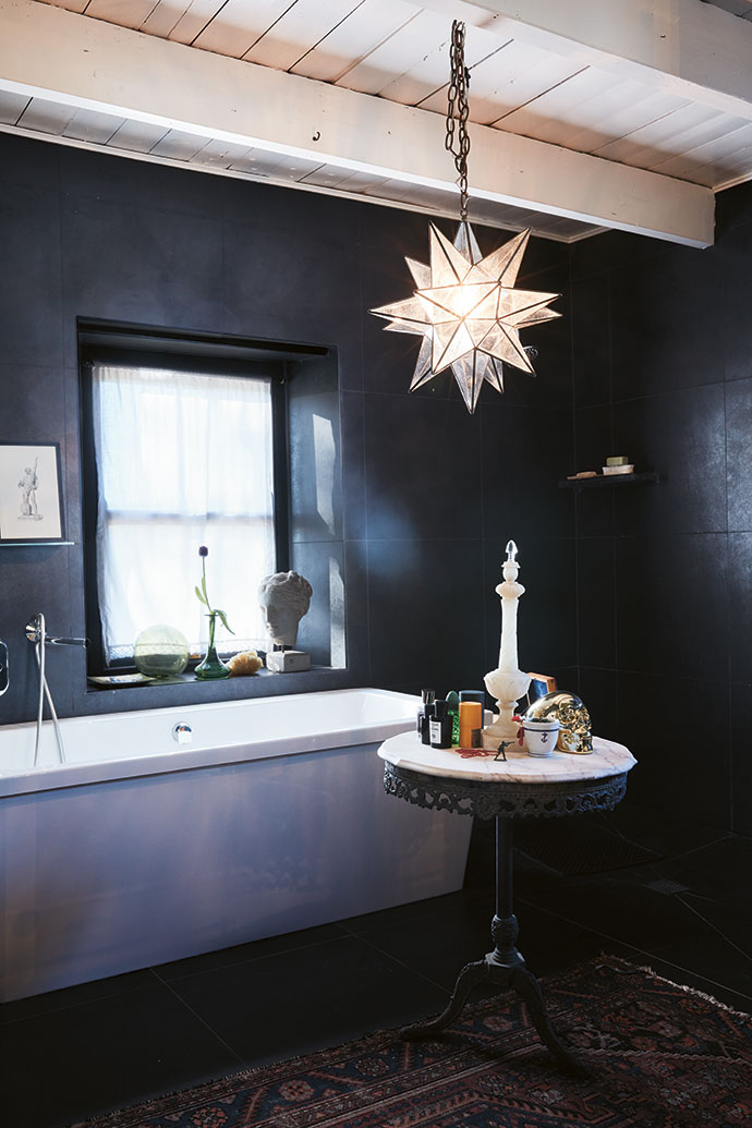 The white-and-black theme of the rest of the house is reversed in this bathroom. The star pendant lamp was made by Hero Stained Glass.
