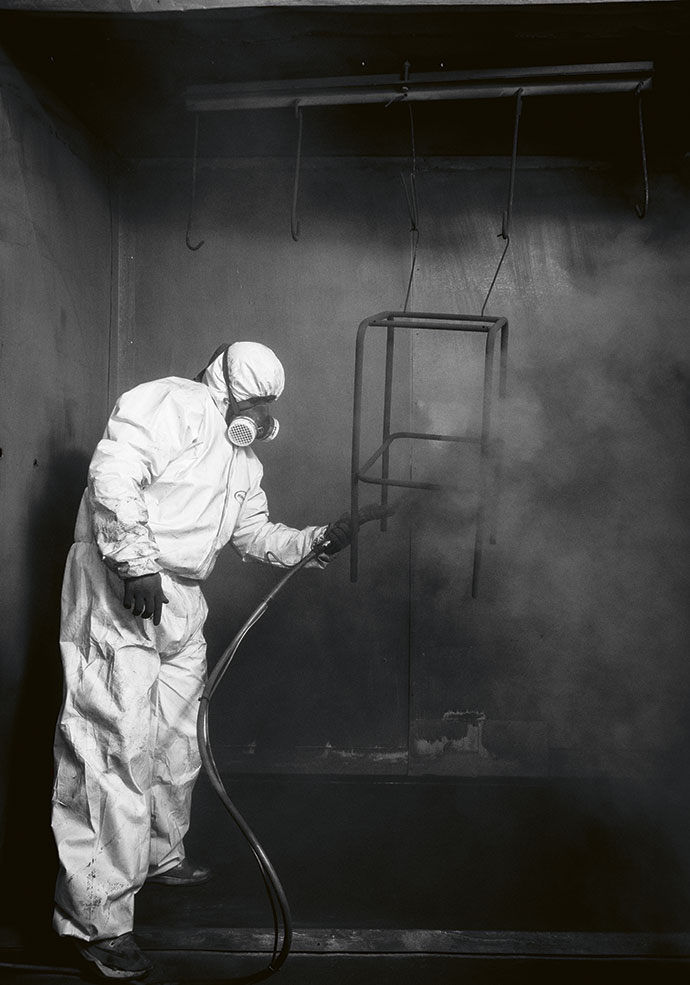 Marshall Williams spray-painting some bar stool metal frames in the Naturalis spray booth.