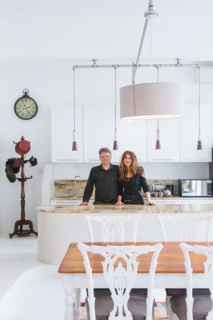 Brian and Cecile in their kitchen. The 19th-century carved wooden hat stand of Scottish origin is befittingly adorned with tartan-covered vintage hats.
