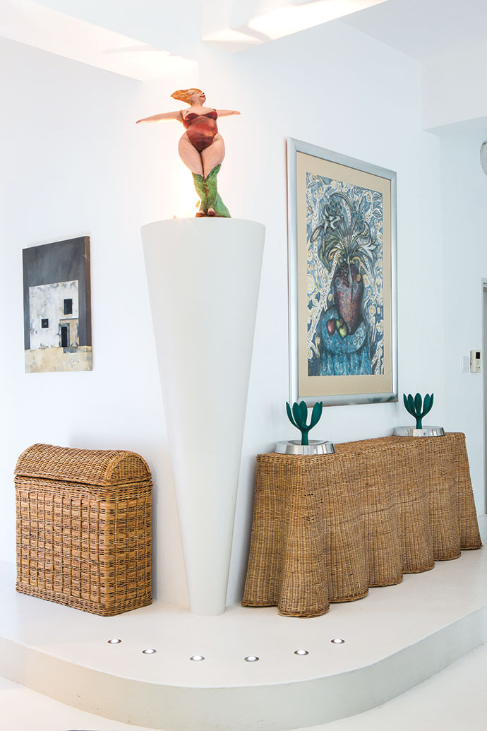 The entrance to the spare bedroom: On top of the wicker table, which is presumably of Malaysian origin but was bought in Edinburgh, stand two Alessi Fruit Mama bowls. The ceramic sculpture was bought in the mid-1990s in Johannesburg. The Ice Store in District 6 painting is one of Brian's own and the other one is by Griet van der Meulen.