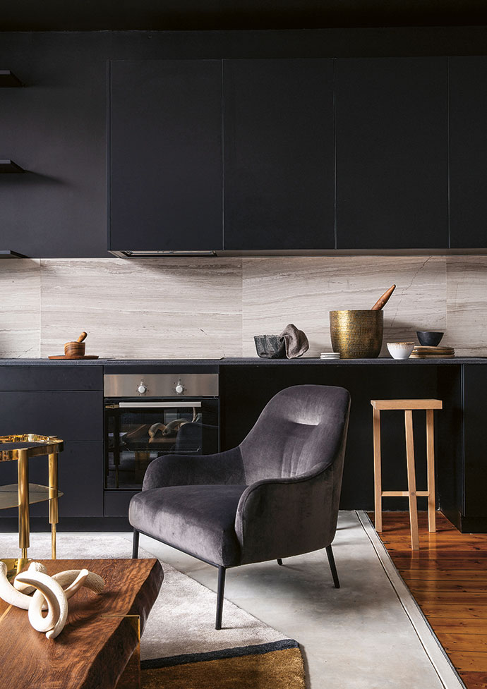 A monochromatic tone is again evident in the kitchen – granite and marble were used to add subtle pattern to the space. A Bijou brass side table by designer Adam Court for OKHA mirrors the brass leg detail of the OKHA coffee table and contrasts with a grey Weylandts armchair. The rug, also from OKHA, picks up both shades.