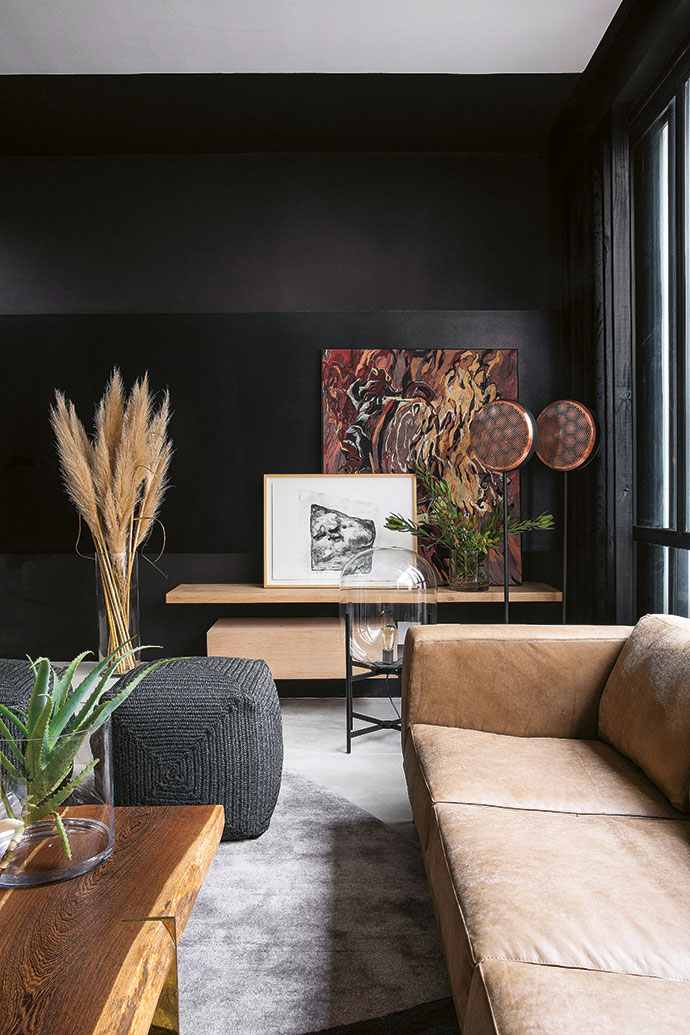Black walls allow artworks from Smith Gallery to pop. The different textures of a leather sofa from Klooftique, a wooden coffee table with brass legs from OKHA and punched-copper floor lamps from Weylandts create interest.