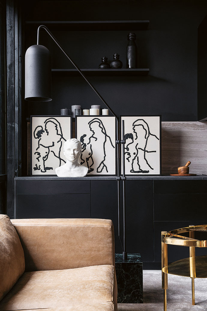 Black-and-white graphic art from Smith Gallery stands out against the satin black kitchen units, and a Giant Moa floor lamp with a marble base by Bofred gives a sense of gravitas and stature.