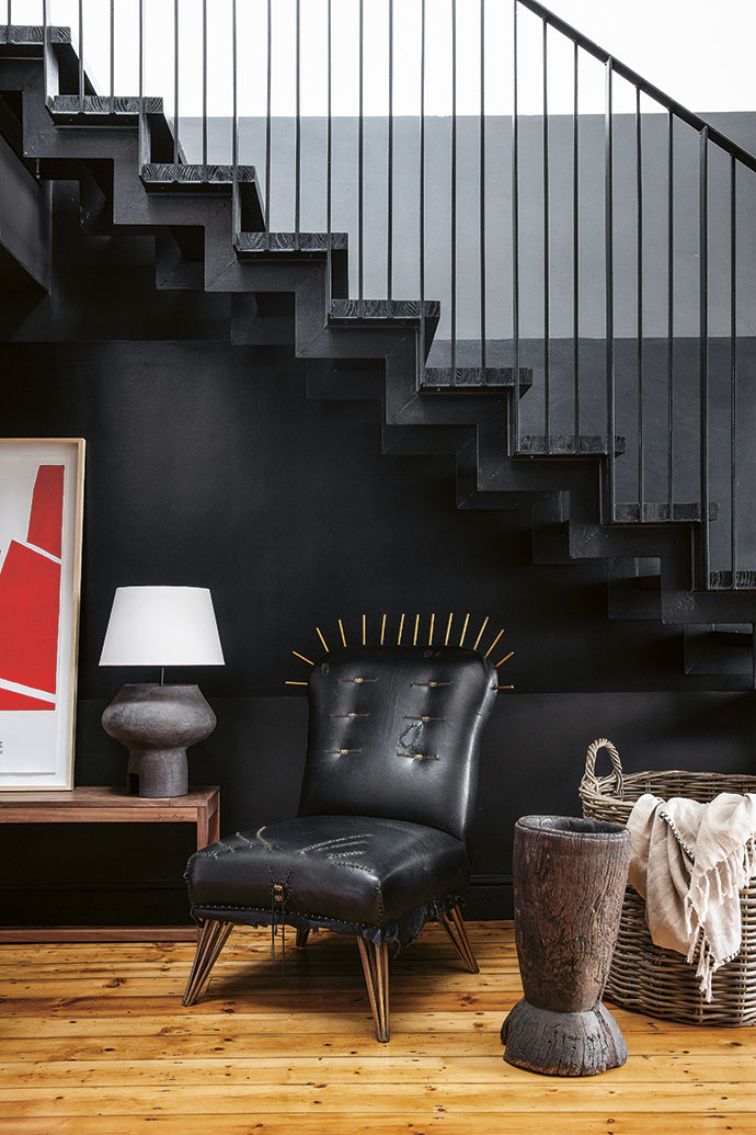 The staircase in black timber and steel is complemented by the Zulu armchair with leather and metal details by Casamento. Artworks add colour to the space, and accessories by Klooftique allow for hidden storage spaces.